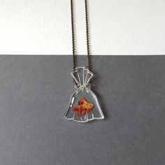 A truly original piece of goldfish jewellery, like a 2D version of a glass bottle or terrarium necklace. Meet Darwin the goldfish, fresh from the funfair or carnival or pet shop. Wherever he came from, hes hoping to meet a loving owner to take him on adventures! Featuring my original illustration durably printed on laser cut clear acrylic. The bag measures 3.5cm (1.4in) across at the widest point, and is 5cm (2in) tall. Darwin is also available in a fish bowl, complete with weeds and mini…