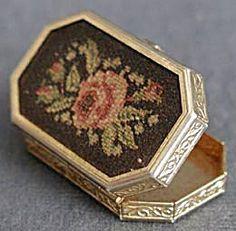 Petit Point Solid Perfume Compact. Tra gli anni 60 e 70, Avon realizzò una serie di piccole scatole ricamate a piccolo punto con le essenze di alcuni suoi profumi (Topaze del 1959, Somewhere del 1961, Occur! del 1962). Qui ce n'è un esempio, completo di confezione: http://lesparfumsdesyssy.over-blog.com/categorie-12588443.html (io ho Topaze e il disegno del ricamo è proprio identico a quest'ultimo con Occur quindi probabilmente i disegni erano casuali e non specifici per ogni essenza)