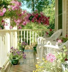 I love front porches! Pretty porch with all the flowers!