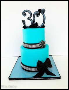 A blinged out teal and black cake with ribbon roses and a bow to celebrate a 30th Birthday in style!