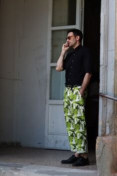 Perfectly balanced black short sleeved  and bright green printed pants rolled just above the ankle.