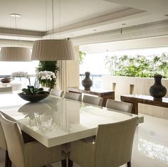 Sala de jantar de uma cobertura dúplex em São Paulo. Mesa em laca branca e aparadores em madeira fazem um contraste harmonioso. Projeto Debora Aguiar