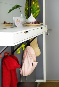 Keep everything you bring to work in the same place to make your mornings a little less stressful. Decorative hooks and a small shelf with drawers provide just the right amount of storage without cluttering your entryway.