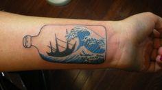 Tatuaje de una botella con un barco y olas