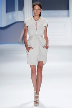 White super piqué sleeveless peplum coat with oversized hood and cutout pockets over white textured silk slip dress.