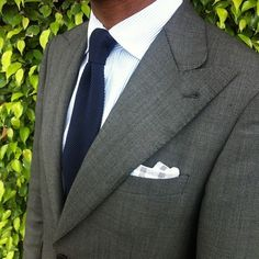 Dark grey jacket with peak lapels, white shirt with light blue dress stripes, navy grenadine tie