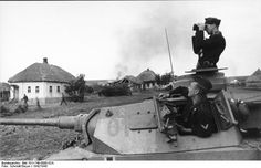 A German Panzer III Division passes through a burning Russian village.
