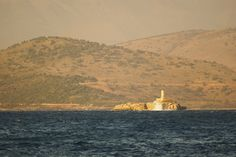 Caparelli islet with the lighthouse. View from Kassiopi harbor. In the background the mountains of Albania.