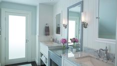Chic master bathroom boasts his and her washstands topped with white marble under white beveled mirrors on vertical paneled walls flanking a gray make up vanity under gray vanity mirror illuminated by uplight sconces.