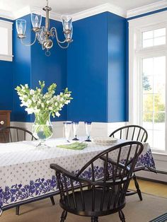 White trim and knockout blue walls brighten up a formal, traditional dining room.
