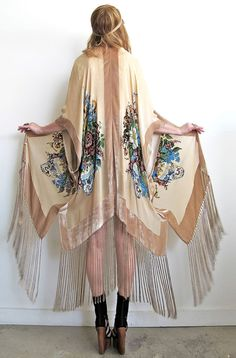 Stunning 1920's art deco inspired kimono. Beautiful long silk flowing fringe all around bottom. Gorgeous floral design in front and back with hand beading on a very high quality silk velvet burnout. Hangs open, with no closures with an effortless and ultra flattering drape.Available in Lilac