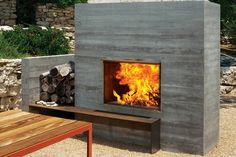 Modern outdoor fireplace area with wooden benches | Dwell