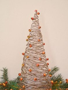 This fun Christmas tree is made with nothing but garden twine and regular white glue. Cover a styrofoam cone with plastic wrap to create a mold for your tree. Dip lengths of twine into white glue and wrap them around the cone, making sure the twine overlaps to strengthen the final tree. Let the glue dry completely, and gently pull out the mold. Decorate your finished tree with bright red berries for a festive touch.