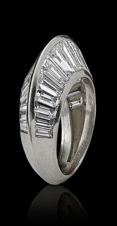 Suzanne Belperron for René Boivin - An Art Deco platinum and diamond ring, Paris, circa 1932. The geometric platinum and diamond 'Crête' ring with thirty tapering trapezoidal diamonds, the two rows of diamonds arranged vertically and sloping towards each other, creating a crest.