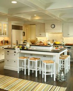 White Shaker inset cabinets, black honed granite countertops and subway-tiled walls add up to a Hamptons-style kitchen. Coffers give the high white ceiling dimension, contrasting the smooth, dark hardwood floors.