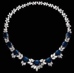 Sapphire and diamond necklace.  The front is designed as a line of graduated oval-cut sapphires, the central sapphire enhanced by a marquise and pear-shaped diamond frame, joined by marquise and pear-shaped diamond links to an oval and pear-shaped diamond backchain.  All mounted in 18K white gold, 16 ins.  Total weight of the sapphires and diamonds is approximately 50.50 and 35.00 carats