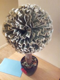 "Money Tree.  Found a 4"" square  at the dollar store and carved it into a ball.  I used paper towel roll and reinforced it with a stick and a pot from the dollar store.  One pack of t-pins and 100 new dollar bills. Bills are first fold the long way then folded in half.  I used a T-pin in only one layer of the bill.  If i do again.  I will include a tutorial."