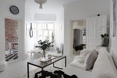 Dla urozmaicenia jasnej i nieco surowej aranżacji salonu zastosowano pojedyncze czarne dodatki, jak chociażby ten w...