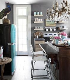 This opulent chandelier and bright vintage refrigerator insert grandeur to a small space. The kitchen island incorporates parts from an antique sideboard. A peacock stands on guard over guests.