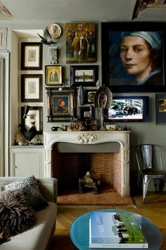 this person is interesting. // wall art, art wall, portrait, ornate fireplace, fireplace, furry pillow, decorative pillows, metal bucket chair, oval coffee table, mantel styling