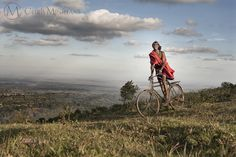 A Maasai Warrior rides home on his bike at sunset over the Ngong Hills.
