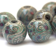Ancient - Large, Round Lampwork Glass Beads, Reactive Multicolor Glass with Silvered Ivory (9). $81.00, via Etsy.