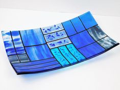 This plate is one from a collection A Gentle Color Mix. All plates in this collection share the same pattern and decorative elements, but each have a unique colorful design. The surface is split in several rectangles combined in pairs or trios which have something in common. it can be a