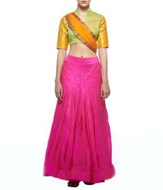 This ensemble features a vibrant pink silk paneled lehenga worn with a textured green blouse with gold kanji varam sleeves. An orange chiffon dupatta with a gold kanjivaram border completes the look.