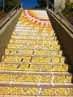 Tiled Yellow Mosaic of the Sun on the steps of an outdoor staircase in…