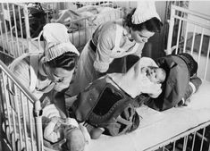 Nurses remove babies from their gas respirators following a gas drill at a London hospital, 1940.