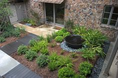 Compact Courtyard with elements needed in back courtyard - rock drain, wood slat walkway, sugar kettle pond fountain