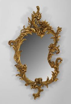 French Victorian gilt carved and shaped wall mirror with scroll forms on border with a large scroll pediment