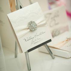 Invitación de bodas elegante con broche de brillantes y lazo de seda