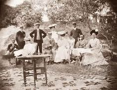 A group of Victorian men and women drink cups of tea whilst picnicking in the gardens of Penshew House. Bangalore, India, circa 1900. Bangalore, Karnataka, India