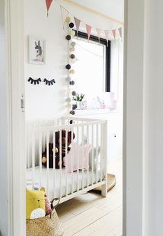 Beautiful nursery featuring sleepy eyes in black, black and white garland, stars pillows