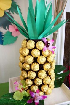 If you're looking for an awesome Hawaiian decoration, look no further... Make a cylinder out of brown card stock and glue Ferraro Roche chocolates all over it. Finish your pineapple off by cutting out some green card stock leaves and gluing them to the top of your decoration so they stick out. Add some pretty tropical flowers and you've got yourself a stunning pineapple candy decoration! See more party ideas and share yours at CatchMyParty.com Luau Theme Party, Hawaiian Party Decorations, Hawaiian Luau Party, Moana Birthday Party, Hawaiian Birthday, Luau Birthday, Hawaiian Theme, Birthday Ideas, Tropical Party Foods