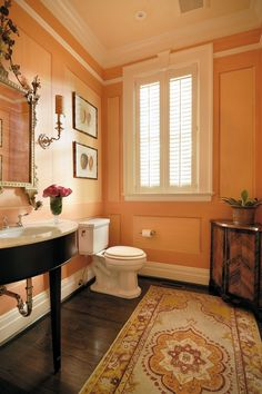 """Artist Kim Comstock Carter created the apricot colored strié treatment on the walls of a powder room in this Lexington (KY) home, designed by Matt Carter and featured in the May/June 2013 issue.  """"I don't like to overuse wallpaper and this is a tongue-in-cheek insinuation of paneling,"""" he said."""