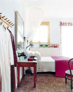 Un dormitorio en blanco. Esta gama, con sus infinitos matices es un telón de fondo que admite muebles y complementos en cualquier tono. En este caso, las pinceladas en fucsia y los toques pistacho y turquesa, logran un conjunto fresco y femenino.