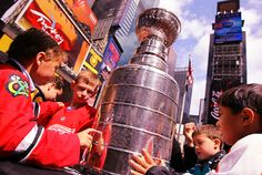 """""""Children touch the Stanley Cup trophy as it sits on display in Times Square on April 11, 2012 in New York City."""""""