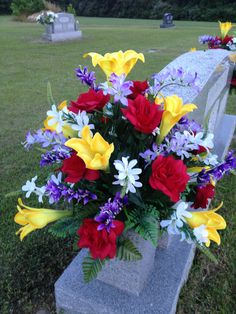 Spring/Summer cemetery vase using yellow lilies, red roses, purple and white filler. May 2015