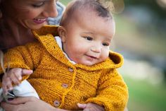 Mustard color baby cardigan - this basic drop sleeve hoodie, while very simple to knit up, will look anything but basic on your little one - find the knitting pattern on LoveKnitting!