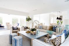 White walls, beige couches, leopard print throw pillows, blue printed throw pillows, blue printed stools, and blue coffee table