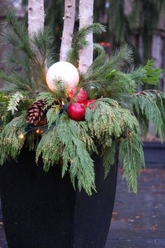 Birch logs, mixed greens, some pomegranates, a big pine cone, stuff the mini lights into the globe lampshade and string some throughout the greens. These birch logs are about 6ft long, and tightly buried and tamped into the planter...Could use clusters of birch branches, curly willow, whatever.
