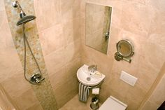 "Small bathroom ( 4' x 4'-6"" ) with shower + sink + toilet combo."