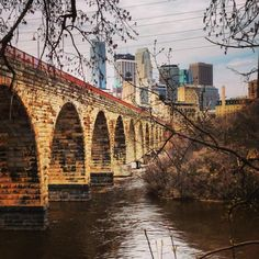 The Stone Arch Bridge is one of our favorite architectural spots in the Twin Cities. The bridge links Father Hennepin Bluffs Park on the east bank of the Mississippi River and Mill Ruins Park and West River Parkway on the west bank. Minneapolis Skyline, Arch Bridge, Modern City, Amazing Adventures, Adventure Travel, Places To Visit, Seed Art, Twin Cities, Footprints