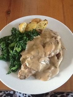 Lambs liver in a mushroom sauce with herb roast potatoes and curly kale