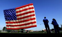 Javier Fernandez, left, and Deanna Wetmore hold a rope as they help a crew flying a hot air balloon draped with the colors of the U.S. flag at Stevens Institute of Technology in Hoboken, New Jersey. (AP)