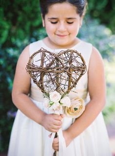 Flower girl holding whimsical wooden heart wand by Camilla Svensson Burns. Photography by Michelle Warren.