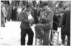 """Παραδοσιακοί οργανοπαίκτες του δήμου Ολύμπου της Καρπάθου, κατά την επίσκεψη του Βασιλιά Παύλου και  της Βασίλισσας Φρειδερίκης. Place: Κάρπαθος  Date Period: 1952-1954  Notes:Η φωτογραφία ανήκει σε φωτογραφικό λεύκωμα με τη σφραγίδα: ΦΩΤΟ-ΡΕΠΟΡΤΑΖ """"ΜΙΝΙΟΝ"""" ΔΙΕΥΘΥΝΤΗΣ ΑΝΤΩΝΙΟΣ ΠΑΤΣΑΒΟΣ ΛΕΚΚΑ 31-ΑΘΗΝΑΙ ΤΗΛ. 31226. Repository: GENNADIUS LIBRARY ARCHIVES Collection Title:     Photographs from the Historical Archives Nikolaos Mavris. http://disjecta.ascsa.net"""