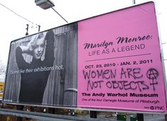 "The Andy Warhol Museum in Pittsburgh just unveiled a huge exhibit of Marilyn Monroe photographs and related art, and a billboard campaign to advertise it. There is a writing on this billboard advertisement; ""Women are not objects."""